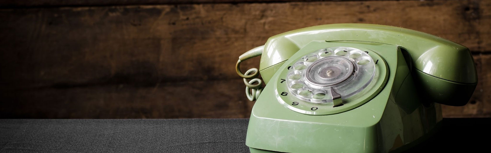 old green phone with wood background